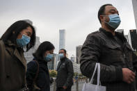 Commuters wearing face masks to help curb the spread of the coronavirus walk out from a subway station during the morning rush hour in Beijing, Thursday, Oct. 29, 2020. (AP Photo/Andy Wong)