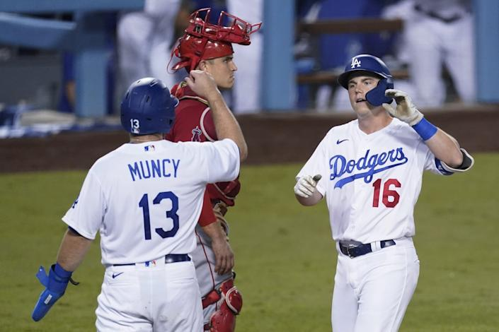 Will Smith is greeted by Max Muncy after hitting a go-ahead, two-run homer for the Dodgers in the fifth inning Friday night.