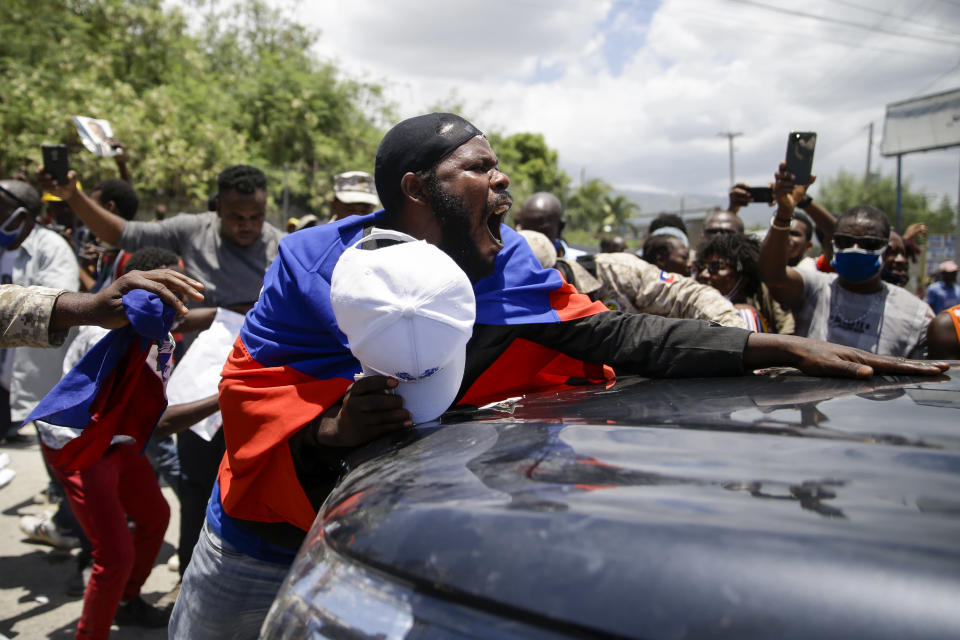 Supporters of former Haitian President Jean-Bertrand Aristide stand in front of a vehicle that is part of the caravan driving him away from the airport after his arrival from Cuba, where he underwent medical treatment, in Port-au-Prince, Haiti, Friday, July 16, 2021. Aristide's return adds a potentially volatile element to an already tense situation in a country facing a power vacuum following the July 7 assassination of President Jovenel Moïse. (AP Photo/Joseph Odelyn)