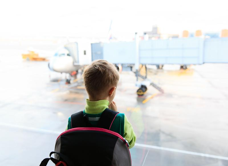 Stock photo of little boy looking at planes in the airport