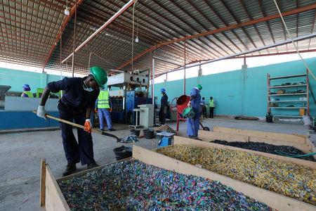 A man shovels shredded plastic litter to be recycled into roofing tiles at the Envirogreen recycling plant in Mogadishu, Somalia January 13, 2019. Picture taken January 13, 2019. REUTERS/Feisal Omar