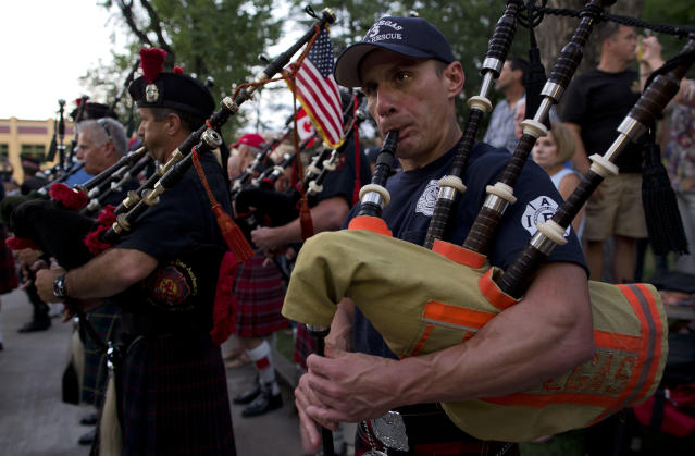 Chris Zaferes, of the Las Vegas Fire Department, plays along with other pipe and drum bands from various fire departments across the country at Courthouse Plaza, Monday, July 8, 2013 in Prescott, Ariz. while practicing for Tuesday's memorial service honoring the 19 Granite Mountain Hotshot firefighters who died fighting a blaze last week near Yarnell, Ariz. (AP Photo/Julie Jacobson)