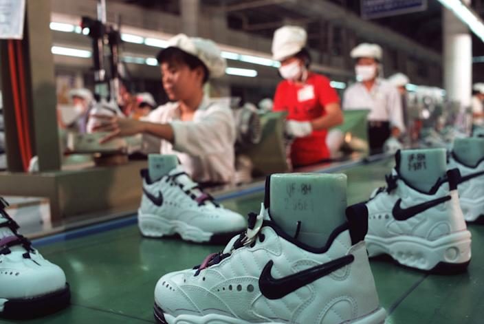 HO CHI MINH CITY, VIETNAM - 1997/08/01: Workers in a Nike factory near Ho Chi Minh City work at a production line conveyor belt, putting together Nike sports shoes.. (Photo by Peter Charlesworth/LightRocket via Getty Images)