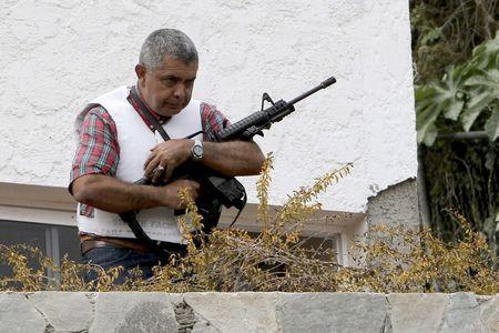 Angel Vivas, a retired army general and anti-President Nicolas Maduro protester, stands in his house with an automatic weapon as he resists being detained in Caracas in this February 23, 2014 file photo. REUTERS/Stringer/Files
