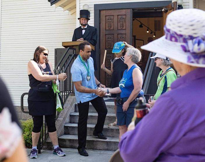 Phillip Thompson, board president and director of the Idaho Black History Museum, shakes hands with Jayne Black as she and members of Boise Galloway Training award $1,600 to the museum from a 10K Juneteenth run the group sponsored. Juneteeth was made a federal holiday this year.