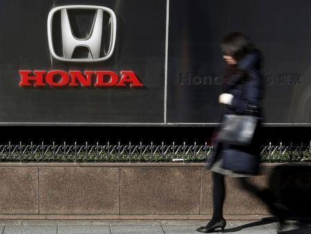 A woman walks past a logo of Honda Motor Co outside the company's dealership in Tokyo, Japan, January 27, 2016. Picture taken January 27, 2016. REUTERS/Yuya Shino