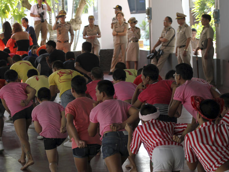 """Thai prison officials, background, watch as inmates do the stretching before performing """"Gangnam Style"""" dance during the dancing competition at a prison in Bangkok, Thailand Tuesday, Nov. 27, 2012. The event was held to encourage inmates to do more exercise and coincide with the concert of South Korean rapper PSY's """"Gangnam Style"""" to be held in Bangkok on Wednesday, Nov. 28. (AP Photo/Apichart Weerawong)"""
