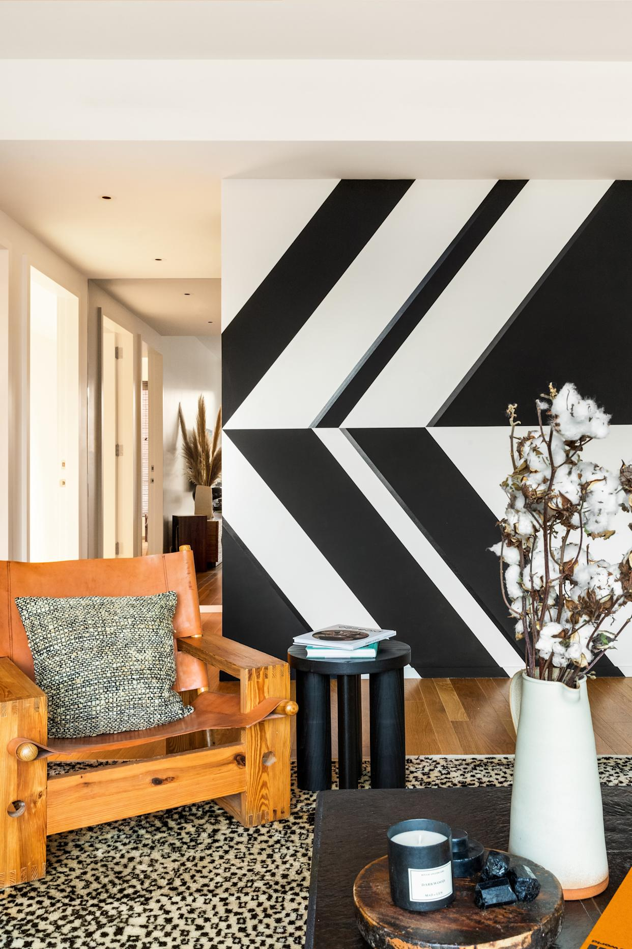 """<div class=""""caption""""> In the living room, Chris Wyrick designed a wall mural inspired by the architecture of Brazilian modernist Oscar Niemeyer. Børge Mogensen chair; side table by Matter. </div>"""
