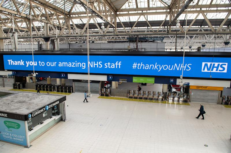 Travellers walk beneath a 'thank you NHS' message displayed at a largely empty Waterloo station, in London, as the UK continues in lockdown to help curb the spread of the coronavirus.