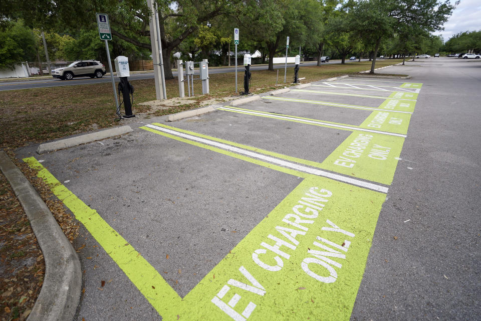FILE - This Thursday, April 1, 2021 file photo shows parking spots with charging stations for electric vehicles at a public park in Orlando, Fla. If the auto industry is to succeed in its bet that electric vehicles will soon dominate the roads, it will need to overcome a big reason why many people are still avoiding them: Fear of running out of juice between Point A and Point B. (AP Photo/John Raoux)