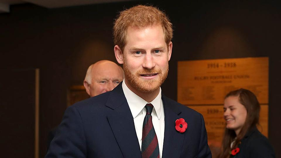 Prince Harry wearing a navy suit with a poppy