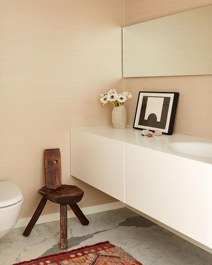 """<div class=""""caption""""> """"I wanted to bring in some natural elements to soften the space,"""" says Bergin of the powder room, which features a <a href=""""https://www.phillipjeffries.com/"""" rel=""""nofollow noopener"""" target=""""_blank"""" data-ylk=""""slk:Phillip Jeffries"""" class=""""link rapid-noclick-resp"""">Phillip Jeffries</a> grasscloth wall covering, an antique Portuguese stool, a <a href=""""https://lusitanostudio.com/"""" rel=""""nofollow noopener"""" target=""""_blank"""" data-ylk=""""slk:Lusitano Studio"""" class=""""link rapid-noclick-resp"""">Lusitano Studio</a> ceramic vase, and a painting by Paul Kopau. </div>"""