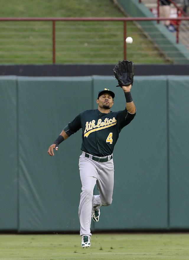 Oakland Athletics center fielder Coco Crisp (4) reaches up to grab a fly out by Texas Rangers' Nelson Cruz in the second inning of a baseball game, Monday, June 17, 2013, in Arlington, Texas. (AP Photo/Tony Gutierrez)