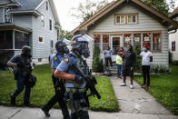 In this image released by World Press Photo, Thursday April 15, 2021, by John Minchillo, Associated Press, part of a series titled Minneapolis Unrest: The George Floyd Aftermath, which won third prize in the Spot News Stories category, shows Protesters and residents watch as police in riot gear walk down a residential street, in St Paul, Minnesota, USA, on May 28, 2020. (John Minchillo, Associated Press, World Press Photo via AP)