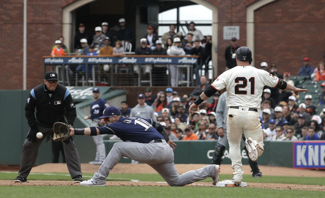 San Francisco Giants' Stephen Vogt (21) reaches safely on his RBI-single as Milwaukee Brewers' Yasmani Grandal (10) waits for the throw during the eighth inning of a baseball game in San Francisco, Saturday, June 15, 2019. (AP Photo/Jeff Chiu)