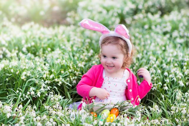 Little girl having fun on Easter egg hunt. Kids in bunny ears and rabbit costume. Children searching for eggs in the garden. Tod