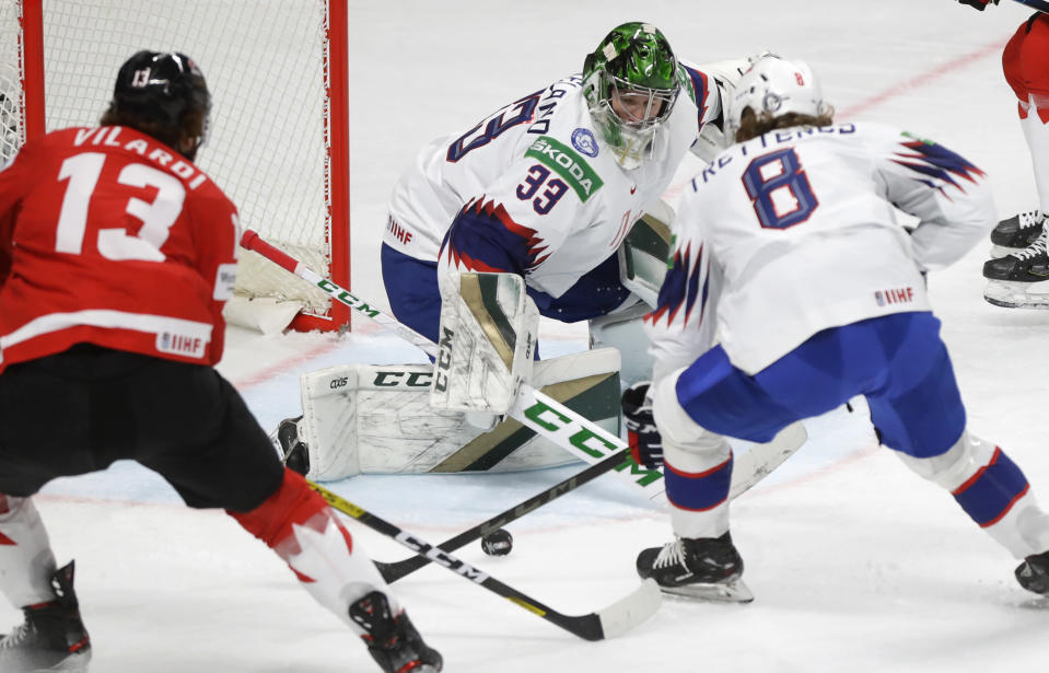 Norway's goaltender Henrik Haukeland blocks a shot by Canada's Gabriel Vilardi, left, during the Ice Hockey World Championship group B match between Canada and Norway at the Arena in Riga, Latvia, Wednesday, May 26, 2021. (AP Photo/Sergei Grits)