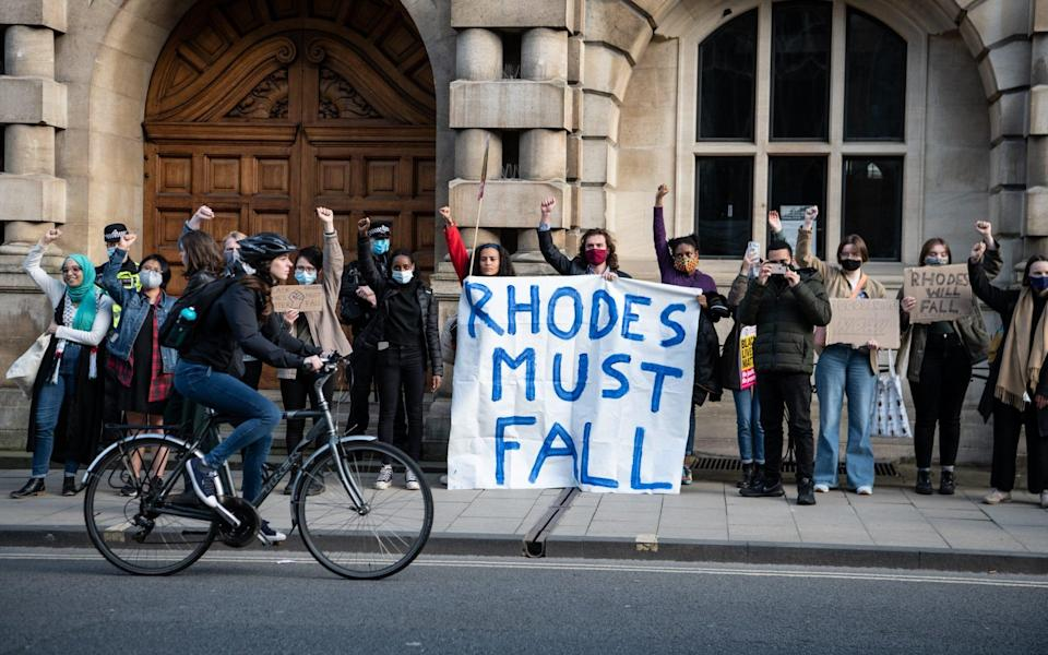 Protesters march to Oriel Colleges statue of Cecil Rhodes at the University of Oxford on May 25, 2021 in Oxford, England - Laurel Chor/Getty