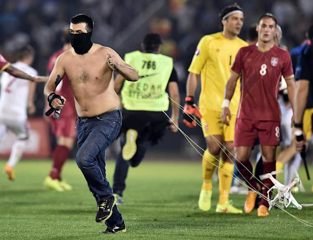A masked Serbian supporter pulls a drone after a flag with Albanian national symbols was flown over the pitch and pulled down by Serbia's players during the EURO 2016 group I football match between Serbia and Albania in Belgrade on October 14, 2014 (AFP Photo/Andrej Isakovic)