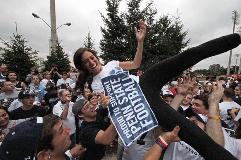 Penn State University freshman Haley Altus, from Media, Pa., is tossed in the air during an early morning pep rally in support of the Penn State football team outside the Lasch Football Building on the school's main campus before the team's morning workout Tuesday, July 31, 2012 in State College, Pa. (AP Photo/Gene J. Puskar)