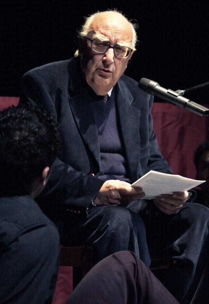 FILE - In this March 5, 2001 file photo, Italian author Andrea Camilleri reads a Luigi Priandello novel at Rome's Piccolo Eliseo theater. Camilleri, known for his popular novels and TV series centered on the much-loved inspector Salvo Montalbano, died in Rome, Wednesday, July 17, 2019, at age 93. Camilleri was Italy's most successful writer, but until he was nearly 70 he had been a virtually unknown author of a handful of historical novels set in his native Sicily. (AP Photo/Gregorio Borgia, File)