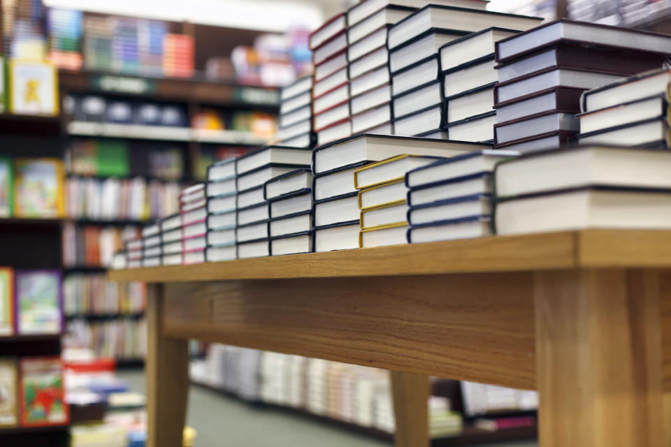 Books stacked on a table for sale at a bookstore.