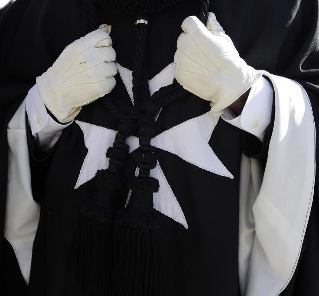 A members of the Knights of Malta wears a dark cloak with a white, eight-pointed Maltese Cross on the front during a procession towards St. Peter's Basilica for a celebration to mark the 900th anniversary of the Order of the Knights of Malta, at the Vatican, Saturday, Feb. 9, 2013. The order traces its history to the 11th century with the establishment of an infirmary in Jerusalem that cared for people of all faiths making pilgrimages to the Holy Land. It is the last of the great lay chivalrous military orders like the Knights Templars that combined religious fervor with fierce military might to protect and expand Christendom from Islam's advance during the Crusades. In February 1113, Pope Paschal II issued a papal bull recognizing the order as independent from bishops or secular authorities, reason for Saturday's anniversary celebrations at the Vatican. (AP Photo/Gregorio Borgia)