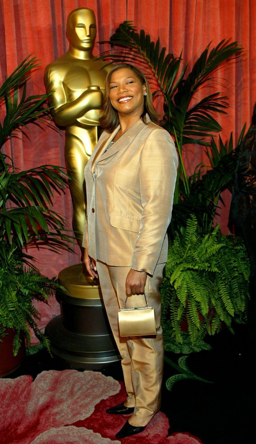 <p>Looks like Queen Latifah got the memo to dress like the Oscar statue at an Academy Awards party in 2003. The actress wore a shiny gold suit and matching purse. </p>