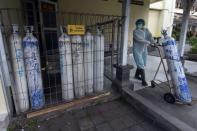 A medical worker pulls an oxygen cylinder to be delivered to the emergency ward at a government-run hospital amid the coronavirus disease (COVID-19) outbreak in Denpasar, Bali