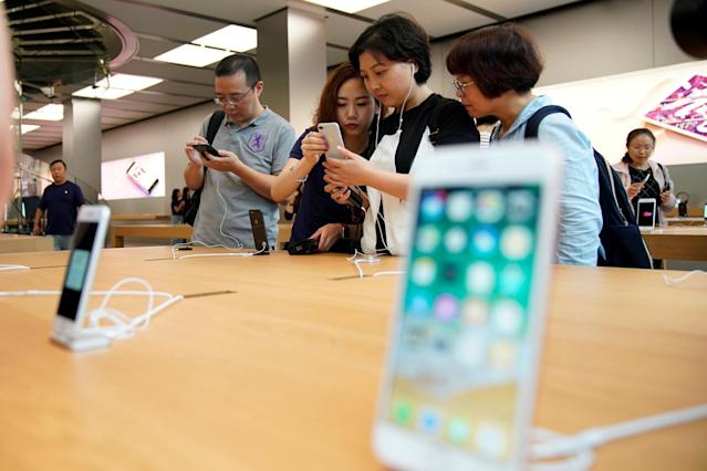 Customers look at Apple's new iPhone 8 Plus after it goes on sale at an Apple Store in Shanghai, China September 22, 2017. REUTERS/Aly Song