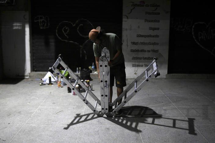 "Street artist Wolfgang Salazar unfolds a portable ladder as he works into the night on his most recent mural in the Boleita neighborhood of Caracas, Venezuela, Saturday, Jan. 9, 2021. Salazar uses the artistic name of Badsura, a play on the English word ""bad"" and the Spanish word ""basura,"" for ""garbage."" (AP Photo/Matias Delacroix)"