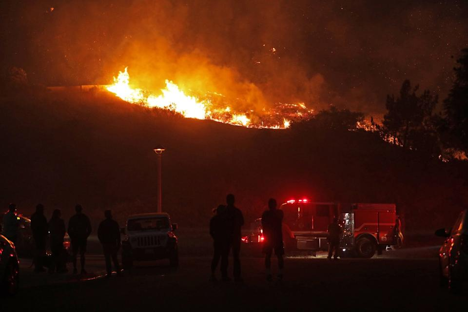 A crowd watches a hillside burn on Foxtail Drive and Lotus Avenue in Yorba Linda.