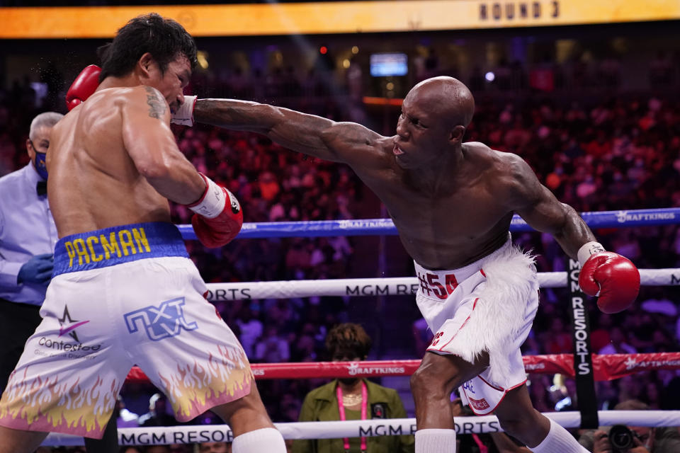 Yordenis Ugas, right, of Cuba, reaches in to hit Manny Pacquiao, of the Philippines, in a welterweight championship boxing match Saturday, Aug. 21, 2021, in Las Vegas. (AP Photo/John Locher)