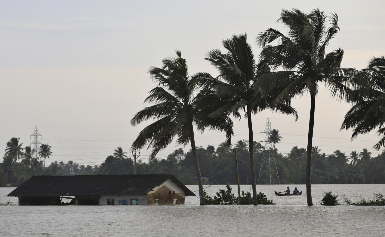 <p>Two men row a boat through a flooded paddy field next to an inundated structure in Alappuzha in the southern state of Kerala, India, Monday, Aug. 20, 2018. Kerala has been battered by torrential downpours since Aug. 8, with floods and landslides killing at least 250 people. About 800,000 people now living in some 4,000 relief camps. (AP Photo/Aijaz Rahi) </p>