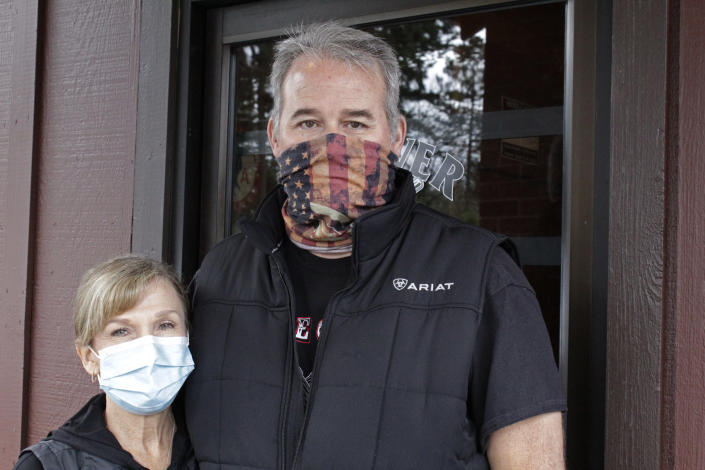 Liz and Bryan Mitchell, co-owners of the Carver Hangar, pose outside their restaurant in Boring, Ore., on Jan. 6, 2021. The restaurant is one of dozens of restaurants around the country defying state bans on indoor dining enacted due to the spread of COVID-19. In Oregon, the defiance has led to a crackdown by state regulators and thousands of dollars in fines for some establishments. (AP Photo/Gillian Flaccus)