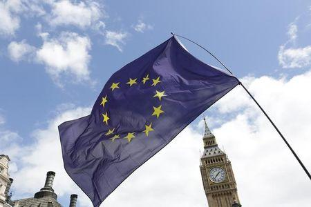 A European Union flag is held in front of the Big Ben clock tower in Parliament Square during a 'March for Europe' demonstration against Britain's decision to leave the European Union, central London