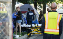 A city-sponsored sweep is carried out on an encampment of individuals living along Grant Street at Sixth Avenue south of downtown Denver on Wednesday, July 7, 2021. (AP Photo/David Zalubowski)