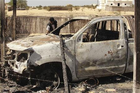 A man inspects the wreckage of a burnt car after assaults on militants by the Egyptian Army, in a village on the outskirts of Sheikh Zuweid, near the city of El-Arish in Egypt's Sinai peninsula in this September 10, 2013 file photo. REUTERS/Stringer/Files