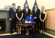 From left, family members Katie Hochul and Matt Gloudeman, Bill Hochul, center, and Will and Christina Hochul watch as Kathy Hochul, the first woman to be New York's governor, signs documents during a swearing-in ceremony in the Red Room at the state Capitol, early Tuesday, Aug. 24, 2021, in Albany, N.Y. (AP Photo/Hans Pennink, Pool)