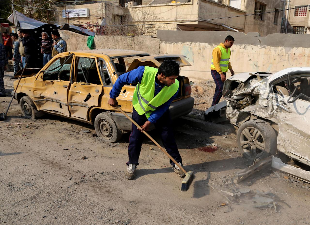Baghdad municipality workers clean up after a car bomb attack near the Technology University in Sinaa Street in downtown Baghdad, Iraq, Wednesday, Jan. 15, 2014. A wave of bombings across Iraq striking busy markets and a funeral north of Baghdad killed tens of people Wednesday, authorities said, as the country remains gripped by violence after al-Qaida-linked militants took control of two cities in western Anbar province. (AP Photo/Karim Kadim)