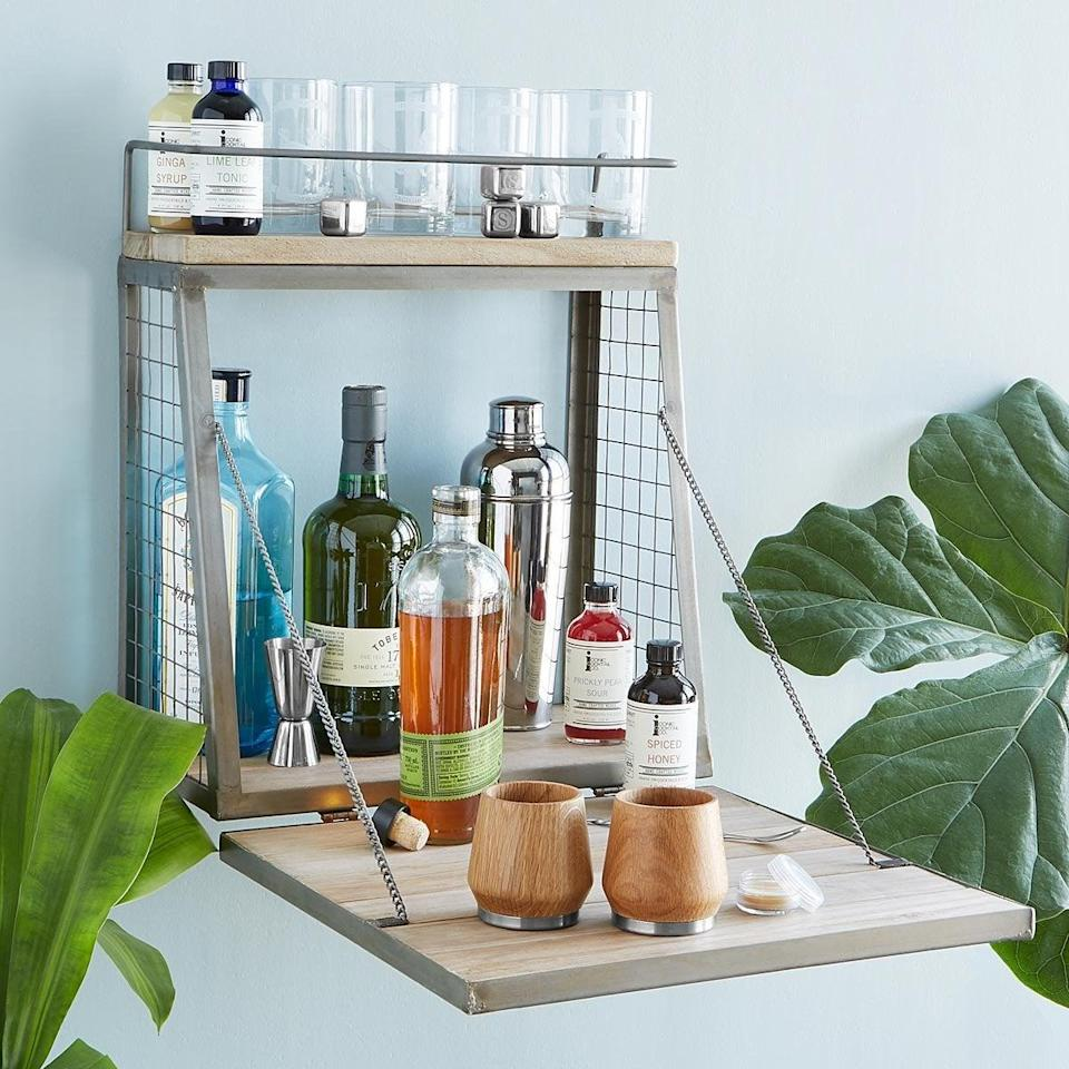 """<h2>Uncommon Goods Hanging Cocktail Bar</h2><br>Right about now, even the smallest of spaces is deserving of its own bar. If you're low on square footage, then consider this fold-out and wall-mounted piece with plenty of glass and cocktail-accouterment storage — even when the bar is <em>not</em> folded out for full-on mixology ventures.<br><br><strong>Uncommon Goods</strong> HANGING COCKTAIL BAR, $, available at <a href=""""https://go.skimresources.com/?id=30283X879131&url=https%3A%2F%2Fwww.uncommongoods.com%2Fproduct%2Fhanging-cocktail-bar"""" rel=""""nofollow noopener"""" target=""""_blank"""" data-ylk=""""slk:Uncommon Goods"""" class=""""link rapid-noclick-resp"""">Uncommon Goods</a>"""