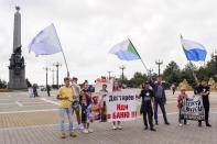 """A small group of demonstrators hold posters reading """"Degtyaryov, go to the bathhouse!!!"""" and """"I'm, we are Sergei Furgal"""" in Khabarovsk, Russia, in the country's Far East, on Saturday, Sept. 11, 2021. A few demonstrators each evening gather in a persistent reminder of the mass protests last year demanding the release of Furgal, the region's former governor, who was replaced by the Kremlin with Mikhail Degtyaryov. (AP Photo/Sergei Demidov)"""