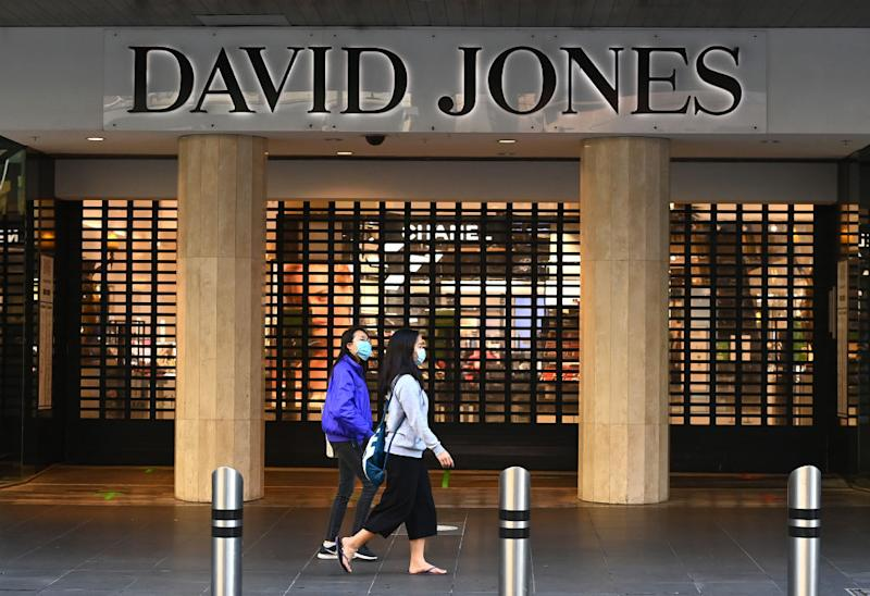 People wearing face masks walk in front of a closed David Jones store in an empty Bourke Street Mall in Melbourne.