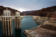 FILE - In this July 28, 2014, file photo, lightning strikes over Lake Mead near Hoover Dam that impounds Colorado River water at the Lake Mead National Recreation Area in Ariz. The Colorado River Indian Tribes Water Resources has played an outsized role in Arizona to help keep Lake Mead from falling to drastically low levels. Still, Arizona is expected to face the first-ever mandatory cuts to its Colorado River water supply in 2022.(AP Photo/John Locher, File)