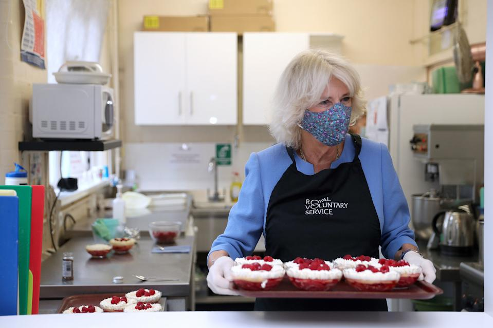 Britain's Camilla, Duchess of Cornwall, in her role as President, Royal Voluntary Service, serves up a trifle dessert as she works in the kitchen during a visit to the Royal Voluntary Service Mill End lunch club in Rickmansworth, Hertfordshire on October 8, 2020, to meet volunteers who have overcome recent challenges posed by the novel coronavirus COVID-19 pandemic to reinstate the much-needed lunch sessions. (Photo by Andrew Matthews / POOL / AFP) (Photo by ANDREW MATTHEWS/POOL/AFP via Getty Images)