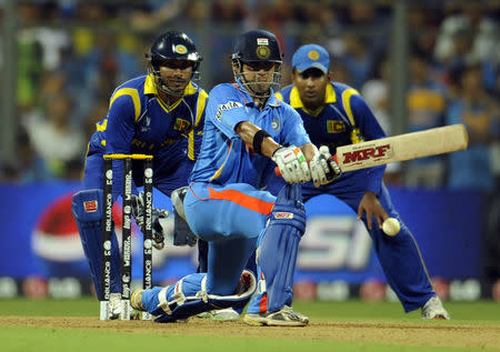 India's Gambhir plays a shot watches by Sri Lanka's Sangakkara and Jayawardene during their ICC Cricket World Cup final match in Mumbai