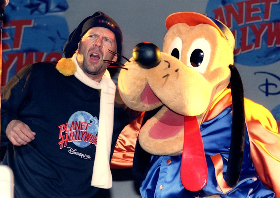 US actor Bruce Willis performs live on stage with a cartoon character during the opening ceremony of Eurodisney's Planet Hollywood Cafe near Paris November 16. It was the Grand Opening of the 38th Planet Hollywood restaurant.
