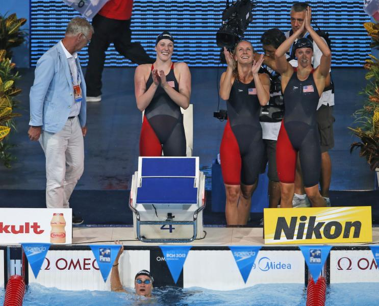 The United States Women's 4x100m medley relay team, from left: Missy Franklin, Jessica Hardy and Dana Vollmer celebrate after Megan Romano, in the water. anchored them to the gold medal at the FINA Swimming World Championships in Barcelona, Spain, Sunday, Aug. 4, 2013. (AP Photo/Daniel Ochoa de Olza)