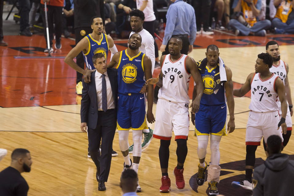 Golden State Warriors forward Kevin Durant (35) walks off the court after sustaining an injury as he is consoled by Toronto Raptors center Serge Ibaka (9) as Warriors forward Andre Iguodala (9) and guard Kyle Lowry (7) look on during first-half basketball action in Game 5 of the NBA Finals in Toronto, Monday, June 10, 2019. (Chris Young/The Canadian Press via AP)