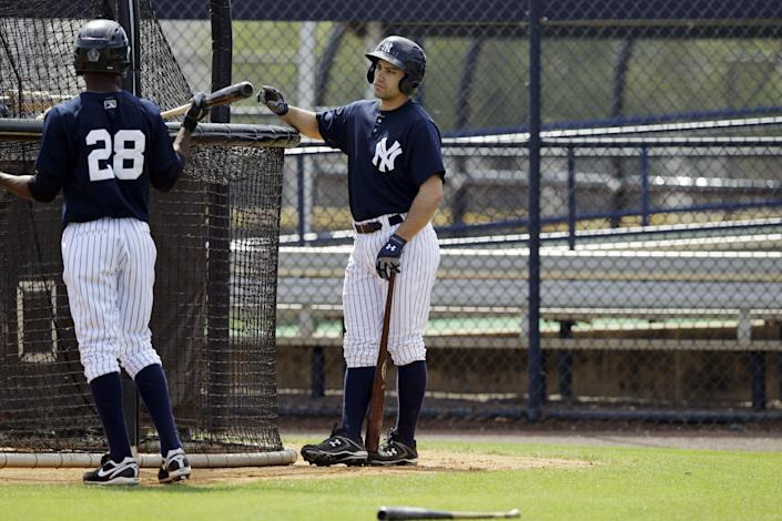 In this Wednesday, March 7, 2012, photo, Kevin Russo, right, in his fourth season with the Scranton/Wilkes-Barre Yankees, talks to a teammate as he waits his turn behind the batting cage at the Yankees' minor league training complex in Tampa, Fla. Forced out of PNC Field because of a $40 million stadium renovation, the Triple-A Yankees will play 144 games on the road this year. (AP Photo/Kathy Willens)